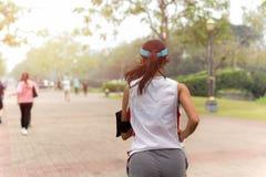 Mujer deportiva joven que corre en el pavimento del parque de la ciudad que escucha MU Foto de archivo libre de regalías