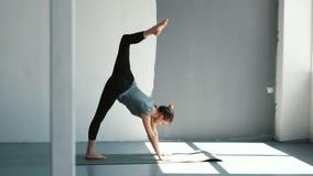 Mujer deportiva joven que estira y que hace yoga en casa Hembra de la aptitud que hace estirando entrenamiento en la estera del e almacen de metraje de vídeo