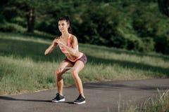 Mujer deportiva joven que hace ejercicios agazapados con la goma al aire libre Fotografía de archivo