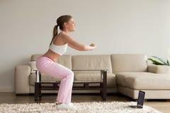 Mujer deportiva joven que hace ejercicios agazapados en casa, trainin en línea Foto de archivo