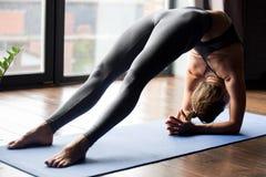 Mujer deportiva joven que hace el ejercicio del puente del codo, cierre para arriba foto de archivo libre de regalías