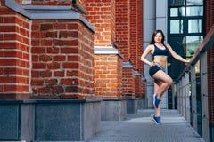 Mujer deportiva joven que hace un ejercicio que estira en la ciudad Imagen de archivo libre de regalías