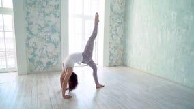 Mujer deportiva joven que hace yoga del ashtanga en estudio con el piso de madera y las ventanas grandes Concepto de la libertad, almacen de metraje de vídeo