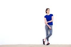 Mujer deportiva joven que mira fijamente y que se inclina contra la pared blanca Fotos de archivo