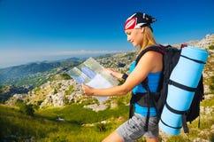 Mujer en la montaña que mira en mapa Imagen de archivo libre de regalías