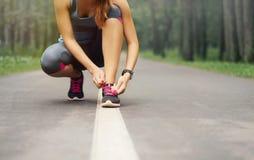 Mujer deportiva joven que se prepara para correr por mañana de niebla temprana en th Fotos de archivo libres de regalías