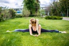 Mujer deportiva joven que se sienta en la hierba en el parque, fracturas gimnásticas Imagen de archivo