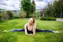 Mujer deportiva joven que se sienta en la hierba en el parque, fracturas gimnásticas Fotos de archivo