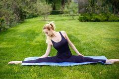 Mujer deportiva joven que se sienta en la hierba en el parque, fracturas gimnásticas Foto de archivo libre de regalías