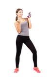 Mujer deportiva joven que sostiene las campanas mudas que tientan en la cámara Fotografía de archivo libre de regalías