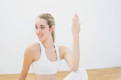 Mujer deportiva magnífica que hace la actitud de la yoga que se sienta en piso Fotografía de archivo libre de regalías