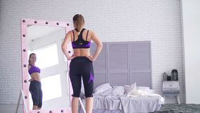 Mujer deportiva que admira su forma del cuerpo en espejo almacen de video