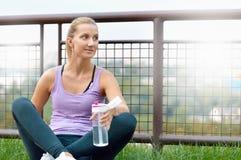 Mujer deportiva que bebe en parque después de activar imagen de archivo libre de regalías