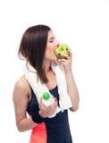 Mujer deportiva que come la manzana y que sostiene la botella con agua Foto de archivo