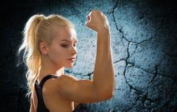 Mujer deportiva que dobla y que muestra el bíceps de la parte posterior Imágenes de archivo libres de regalías