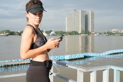 Mujer deportiva que escucha la música con los auriculares en ciudad Imagen de archivo