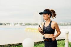 Mujer deportiva que escucha la música con los auriculares en ciudad Fotografía de archivo