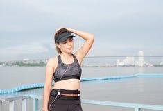 Mujer deportiva que escucha la música con los auriculares en ciudad Foto de archivo libre de regalías