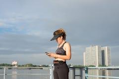 Mujer deportiva que escucha la música con los auriculares en ciudad Fotografía de archivo libre de regalías