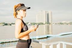 Mujer deportiva que escucha la música con los auriculares en ciudad Fotos de archivo
