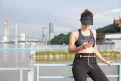 Mujer deportiva que escucha la música con los auriculares en ciudad Imágenes de archivo libres de regalías