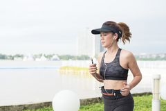 Mujer deportiva que escucha la música con los auriculares en ciudad Foto de archivo