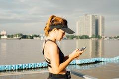 Mujer deportiva que escucha la música con los auriculares en ciudad Fotos de archivo libres de regalías