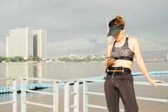 Mujer deportiva que escucha la música con los auriculares en ciudad Imagen de archivo libre de regalías