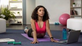 Mujer deportiva que estira después del entrenamiento casero, entrenamiento en línea de la aptitud, salud fotografía de archivo