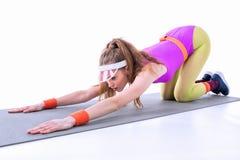Mujer deportiva que estira en la estera del entrenamiento Imágenes de archivo libres de regalías