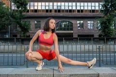 Mujer deportiva que estira y que calienta las piernas antes de funcionar con entrenamiento urbano de la aptitud Deporte y concept imagenes de archivo