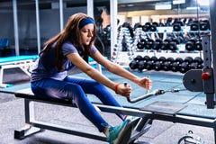 Mujer deportiva que hace ejercicio físico usando el aparato del entrenamiento Foto de archivo
