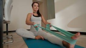 Mujer deportiva que hace ejercicios con aptitud apretada de la banda en casa dentro almacen de metraje de vídeo