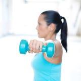 Mujer deportiva que hace la extensión del tríceps Solamente mano y pesa de gimnasia en foco Fotos de archivo
