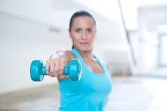 Mujer deportiva que hace la extensión del tríceps Solamente mano y pesa de gimnasia en foco Imagenes de archivo