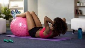 Mujer deportiva que hace sentar-UPS con la bola de la aptitud de las piernas, ejercicio físico, energía imágenes de archivo libres de regalías