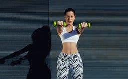 Mujer deportiva que lleva a cabo pesos con las manos para arriba en su frente que consigue los brazos en gran forma Imagen de archivo