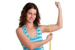 Mujer deportiva que mide su bíceps Foto de archivo