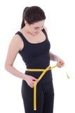 Mujer deportiva que mide su cintura aislada en blanco Fotos de archivo