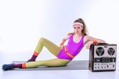 Mujer deportiva que miente en la estera del entrenamiento cerca del tocadiscos retro Imagenes de archivo