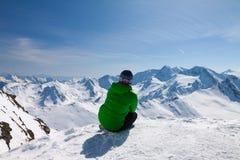 Mujer deportiva que mira para nevar montañas Foto de archivo