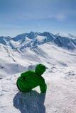 Mujer deportiva que mira para nevar montañas Fotos de archivo libres de regalías