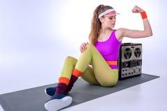 Mujer deportiva que muestra los músculos mientras que se sienta en la estera Imagen de archivo libre de regalías