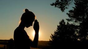 Mujer deportiva que ruega en parque en la puesta del sol imagen de archivo