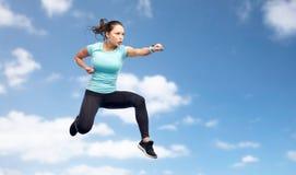 Mujer deportiva que salta en actitud que lucha sobre el cielo Fotos de archivo libres de regalías