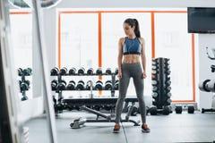 Mujer deportiva que se coloca con los brazos abajo en gimnasio de la aptitud Imágenes de archivo libres de regalías