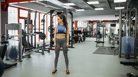 Mujer deportiva que se coloca con los brazos abajo en gimnasio de la aptitud Imagenes de archivo