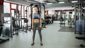 Mujer deportiva que se coloca con los brazos abajo en gimnasio de la aptitud Fotos de archivo libres de regalías