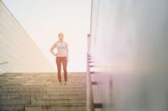 Mujer deportiva que se coloca encendido en escaleras de la ciudad imagen de archivo libre de regalías