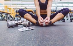 Mujer deportiva que se sienta con pesas de gimnasia y smartphone Fotos de archivo libres de regalías